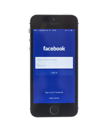 social networking service: Swindon, Reino Unido - 08 de junio 2014: iPhone 5 S mostrando Facebook login pantalla sobre un fondo blanco, Facebook es un servicio de redes sociales en l�nea, fundada en febrero de 2004 por Mark Zuckerberg Editorial