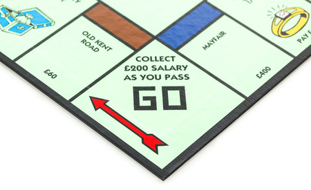 SWINDON, UK - JUNE 11, 2014: English Edition of Monopoly showing Pass Go,  The classic trading game from Parker Brothers was first introduced to America in 1935.