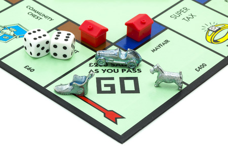 trading board: SWINDON, UK - JUNE 11, 2014: English Edition of Monopoly showing Pass Go,  The classic trading game from Parker Brothers was first introduced to America in 1935.