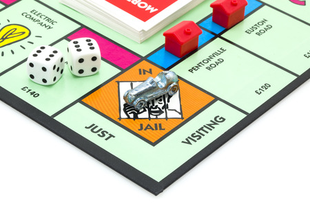 trading board: SWINDON, UK - JUNE 11, 2014: English Edition of Monopoly showing The Jail,  The classic trading game from Parker Brothers was first introduced to America in 1935.