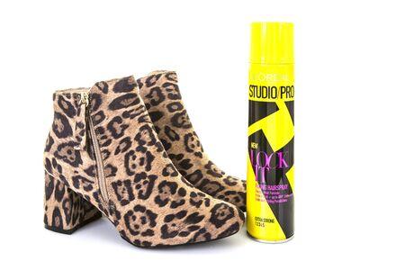 Swindon, Verenigd Koninkrijk - 4 december 2016: Paar luipaardhuid laarzen met een blikje Loreal Studio Pro Lock It haarspray