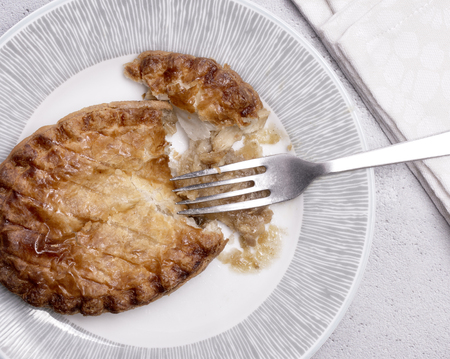 Overhead View of a Chicken pie on a plate with fork and napkin. Zdjęcie Seryjne