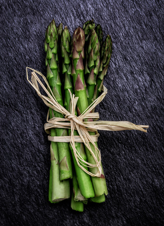 Bunch of Fresh Organic Asparagus on a rustic slate background