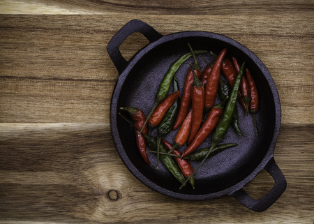 Red and Green Chillies in a black cast Iron bowl on a wooden background with copy space