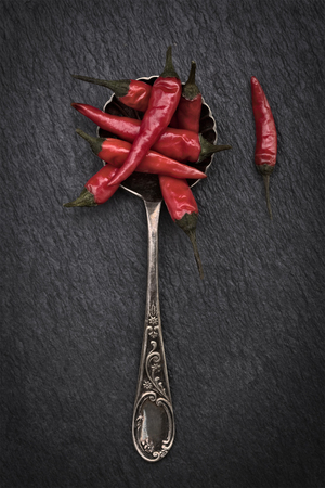 Red and Green Chillies in a spoon on a rustic grey slate background with copy space