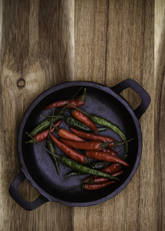 Red and Green Chillies in a black cast Iron bowl on a vertical wooden background with copy space