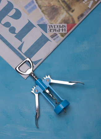 Blue Corkscrew on a blue backgrown with a travel newspaper Zdjęcie Seryjne