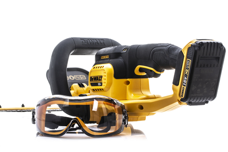 SWINDON, UK - AUGUST 19, 2018: DeWalt cordless Hedge Trimmer and safety glasses on a white background