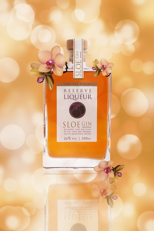 Bottle of Lyme Bay Winery Reserve Liqueur Sloe Gin on a floral background Publikacyjne