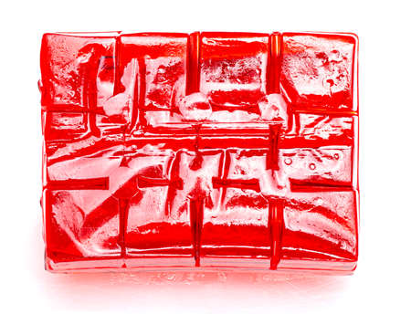 Block of cubes of red strawberry jelly on a white background