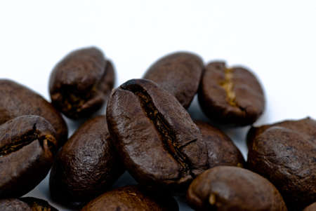 Closeup of roasted coffee beans on whitw surface Stock Photo