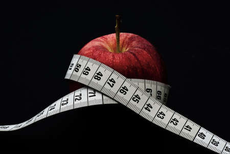 A delicious red apple with at measuring tape around it Stock Photo