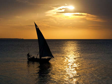 Un bateau de voile dhow dans le coucher du soleil à Zanzibar