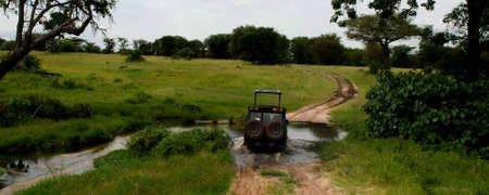 A safari jeep drives through a stream in Serengeti