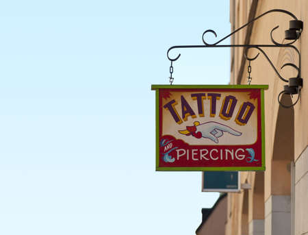 parlor: Tattoo and piercing sign outside tattoo parlor