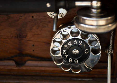 rotary dial telephone: Dialer and wood details of an old phone