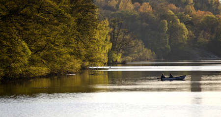 two people in a rowing boat on a lake photo