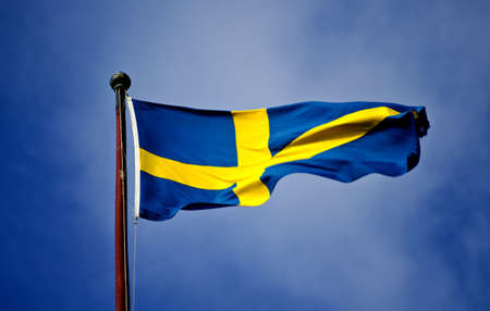 a swedish flag waving in the wind with blue sky photo