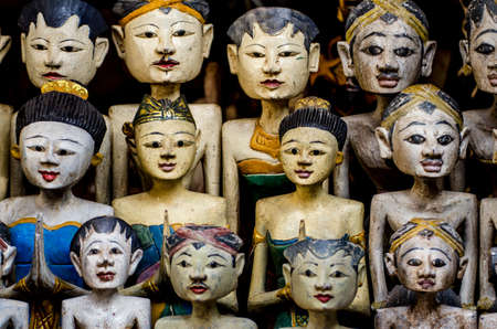 handicrafts: faces of asian wooden dolls in a market Stock Photo