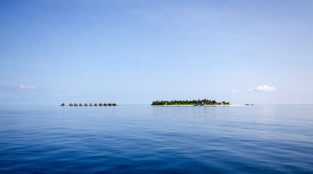A small island in the Maldives with a number of cabins on stilts in the calm blue water photo