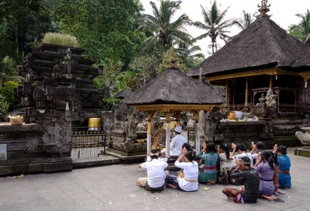 a group of balinese Hindus praying in a temple Editorial