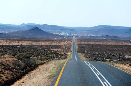 ナミビアの砂漠の景色の丘の上の舗装された道路