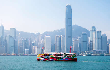 A ferry in Hong Kong harbour with the city skyline in the background