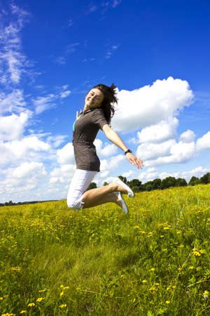 Young smiling woman jumping for joy in the air