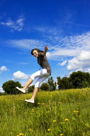 Young woman falls in the air on a flower meadow