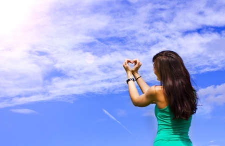 young women formed a heart with her hands in the sky