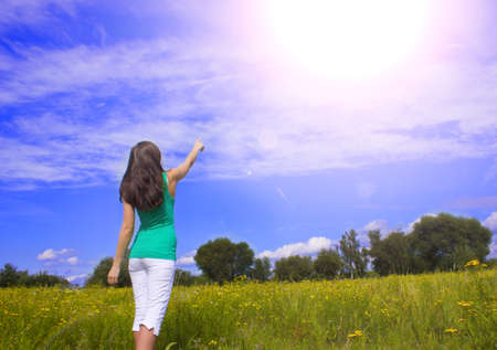 young woman pointing the finger into the sky Stock Photo
