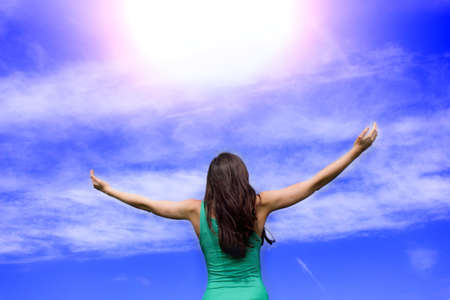 Young woman keeps the arms open into the sky Stock Photo