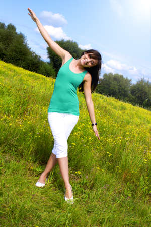 young woman with a beautiful smile smiles on a meadow