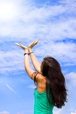A young woman is holding her hands as a v in the sky