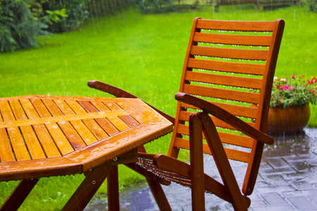 wooden furniture: garden table stands in the rain Stock Photo