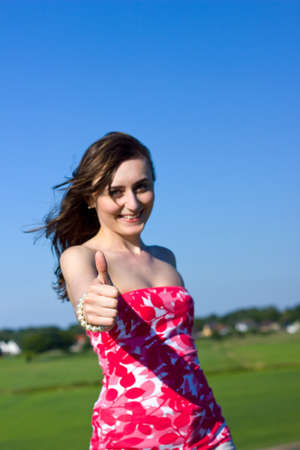 beautiful young woman shows the thumb up