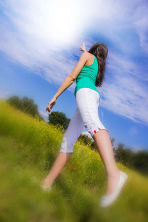 Young woman pointing at the sky