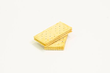 Two butter crackers on top of each other on white background
