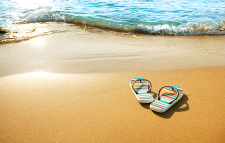 Colorful sandals on beach photo