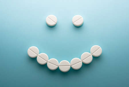 Smiley face  from pills  on blue background Stock Photo - 15256608