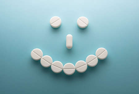 Smile face  from pills  on blue background Stock Photo - 15755182