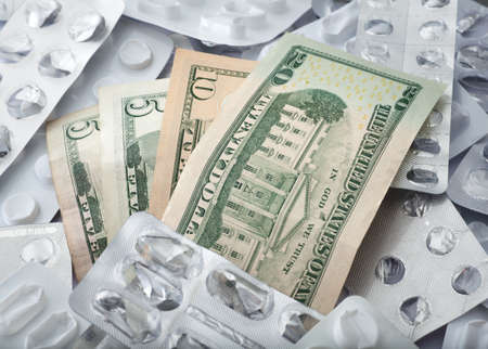 packs of pills: Health costs , empty pill blisters with dollar banknotes background