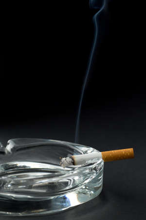 Burning cigarette with ashtray , black bacground