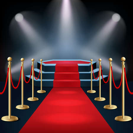 Podium with red carpet and barrier rope in glow of spotlights Archivio Fotografico
