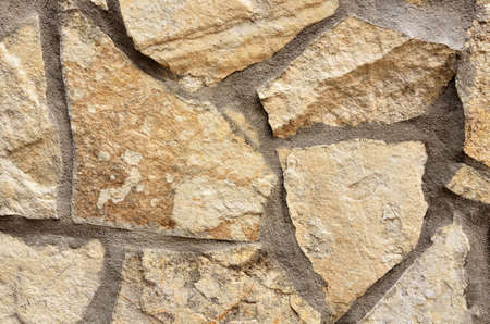 The wall is made of beige stones of various shapes with cement seams.