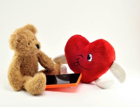Brown Teddy bear toy heart and cell phone with orange case, on white background.