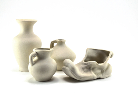 Gift ceramic tableware made of white clay on white background.