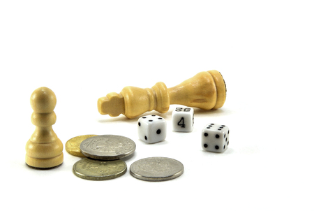 Two wooden chess pieces, coins and dice on white background. 스톡 콘텐츠
