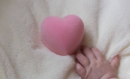 beneficence: Pink heart holding the hand of a small child.