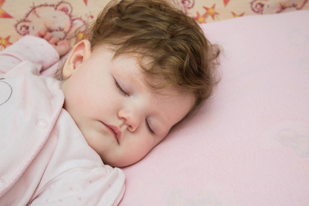 repose: A small child asleep in the crib on a pink background. Stock Photo